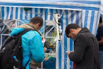 Pakolaisia puhelinten äärellä