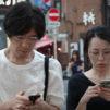 Mies ja nainen katsovat kännyköitään kadulla Tokiossa.