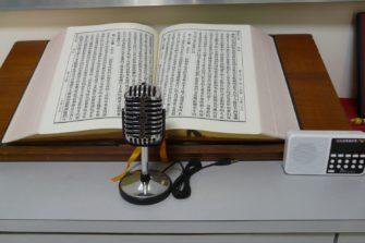 Kiinankielinen avoin Raamattu ja mikrofoni.