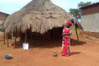 Nainen kotinsa edessä Kamerunissa.