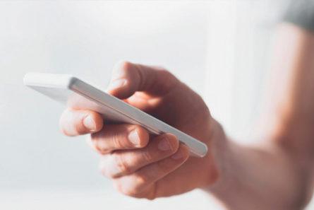 Nainen pitää kännykkää kädessään