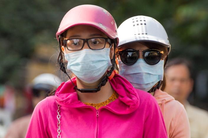Aasialaiset naiset, kypärät ja kasvomaskit.