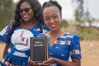 Tansanialainen nainen kädessään uusi raamatunkäännös