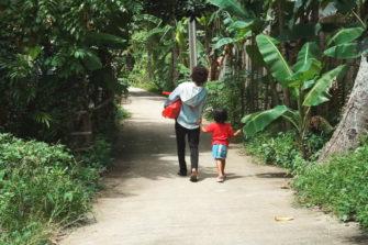 Nainen ja lapsi kävelevät tietä pitkin joulukassiavustus mukanaan.
