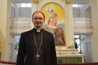 Kirkkoherra Mihail Ivanov Pyhän Marian kirkon alttaritaulun edessä. Kuva: Liliann Keskinen.