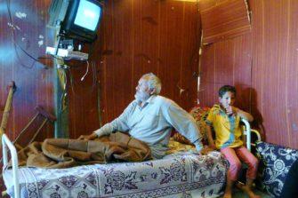 Vanha mies ja poika katsovat tv:tä pakolaisleirillä Libanonissa.