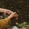 Rukoilevat kädet kasvipenkin tuoreen mullan äärellä