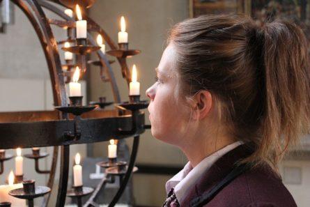 Nainen rukoilee kirkossa maapallokynttelikön edessä.
