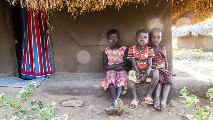 Kolme ugandalaista lasta istuu talon edessä.