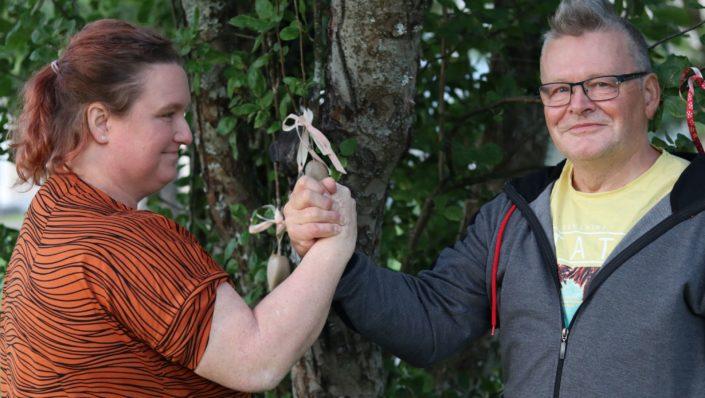 nainen ja mies vääntävät leikillisesti kättä