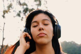Nainen kuuntelee kuulokkeista UT2020:aa